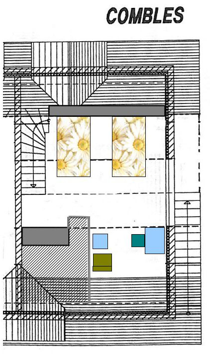 Chambre sous combles avec deux lits et un petit salon.